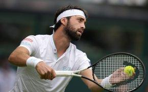 Nikoloz Basilashvili getting ready to serve a ball during a tennis match.