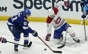Brayden Point moving to front of net with puck, Montreal defender on one knee