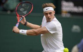 Denis Shapovalov hitting a return during a tennis match at Wimbledon.
