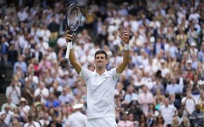 Novak Djokovic celebrating with his hands in the air after winning a match at Wimbledon.