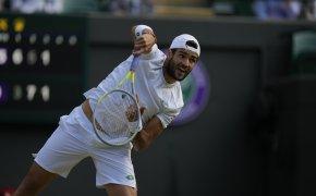 Matteo Berrettini hitting a return during a tennis match at Wimbledon.