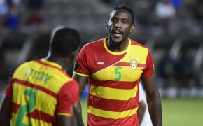 Grenada players talking on the pitch
