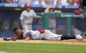 Atlanta Braves' Ozzie Albies stretched out on the ground over home plate after scoring a run during a baseball game.