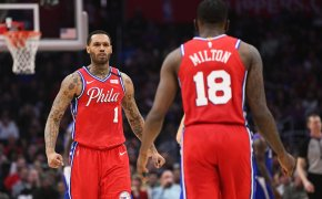 Philadelphia 76ers players Mike Scott and Shake Milton walking towards each other celebrating during a NBA game.