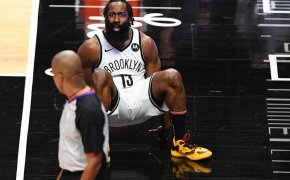 Brooklyn Nets guard James Harden on the ground reacting to a refs call during a game.