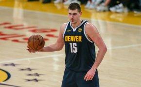 Nikola Jokic holding basketball at top of key