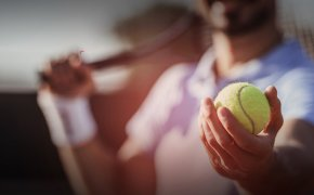 close up image of a tennis player holding a ball