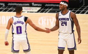 Sacramento Kings players Tyrese Haliburton and Buddy Hield high fiving in celebration during a NBA game on the court.