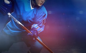 Hockey player in blue jersey with orange hockey stick