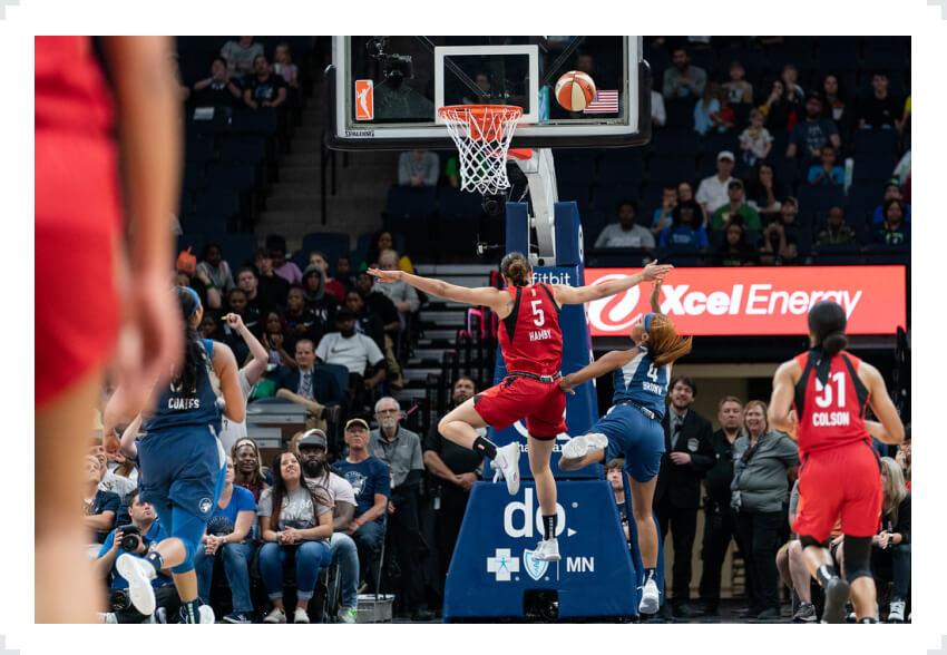 WNBA players jumping through air towards basket