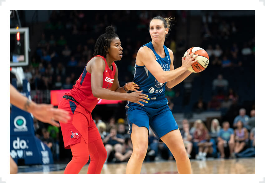 Minnesota Lynx player with ball in hands defended by opponent