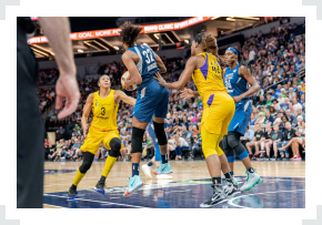 WNBA player with ball in hands defended by opponent