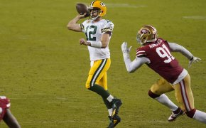 Aaron Rodgers throwing pass as defender chases him