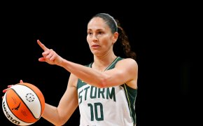 Sue Bird dribbling with right hand, pointing with left hand