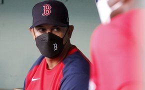 Alex Cora with mask on in dugout