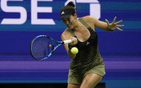 Garbine Muguruza hitting a return against her opponent during a tennis match.