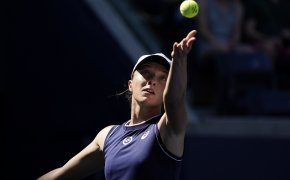 Iga Swiatek throwing the ball up to serve during a tennis match.