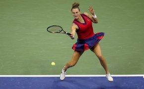Aryna Sabalenka hitting a return shot against an opponent during a tennis match.