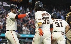 Longoria, Brandon Crawford, and LaMonte Wade Jr. celebrating at home plate