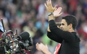 Arsenal's manager Mikel Arteta greeting supporters at the end of a soccer match.