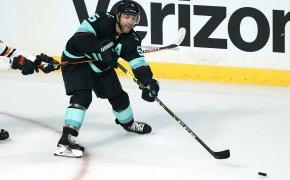 Seattle Kraken's Jeremy Lauzon reaching for the puck during a preseason NHL game.
