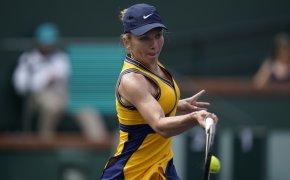 Simona Halep hitting a return shot during a tennis match.