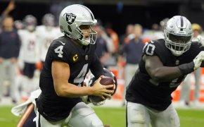 Las Vegas Raiders quarterback Derek Carr running with the ball during an NFL football game.