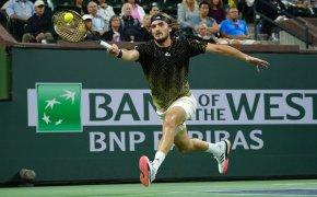 Stefanos Tsitsipas hitting a return shot during a tennis match.