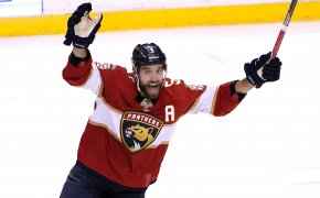 Florida Panthers defenseman Aaron Ekblad celebrating after his teammate scored a goal during an NHL hockey game.