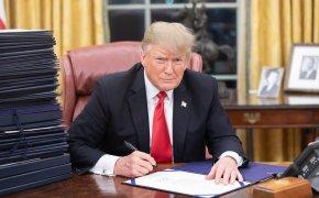 Donald Trump signing documents