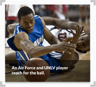 A photo showing an Air Force and UNLV player both reach for a ball during a basketball game