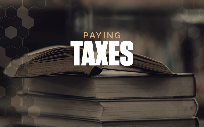 Paying taxes text overlay on stack of books